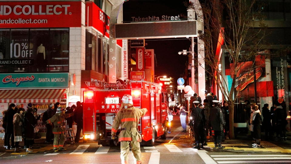 Police and firefighters inspect around the site of a car attack near Takeshita Street in Tokyo, early Tuesday, Jan. 1, 2019. A car slammed into pedestrians early Tuesday on a street where people had gathered for New Year's festivities in downtown Tokyo. (Yuta Omori/Kyodo News via AP)