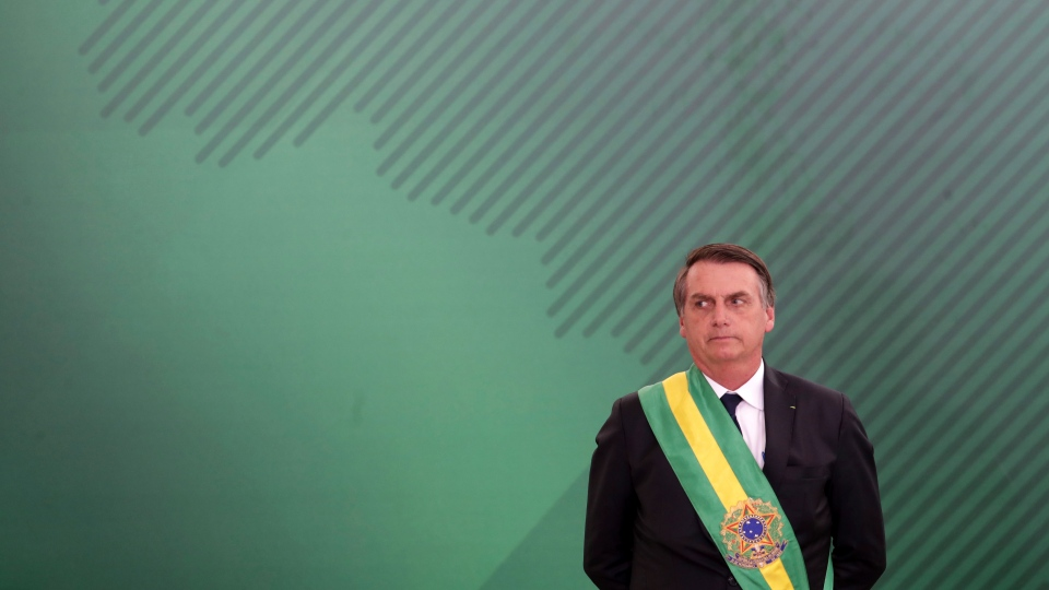 Brazil's President Jair Bolsonaro looks on as he presents his cabinet at the Planalto Presidential palace, in Brasilia, Brazil, Tuesday, January 1, 2019. (AP Photo/Eraldo Peres)