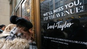 Women peer in the front door of Lord & Taylor's flagship Fifth Avenue store which closed for good, Wednesday, Jan. 2, 2019, in New York.  (AP Photo/Kathy Willens)