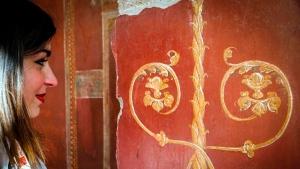 A woman looks at a fresco at the Schola Armaturarum building in Pompeii, Italy, Thursday, Jan. 3, 2019. (Cesare Abbate/ANSA via AP)
