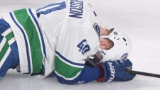 Vancouver Canucks' Elias Pettersson lies injured on the ice after colliding with Montreal Canadiens' Jesperi Kotkaniemi, not shown, during second period NHL hockey action in Montreal, Thursday, Jan. 3, 2019. THE CANADIAN PRESS/Graham Hughes
