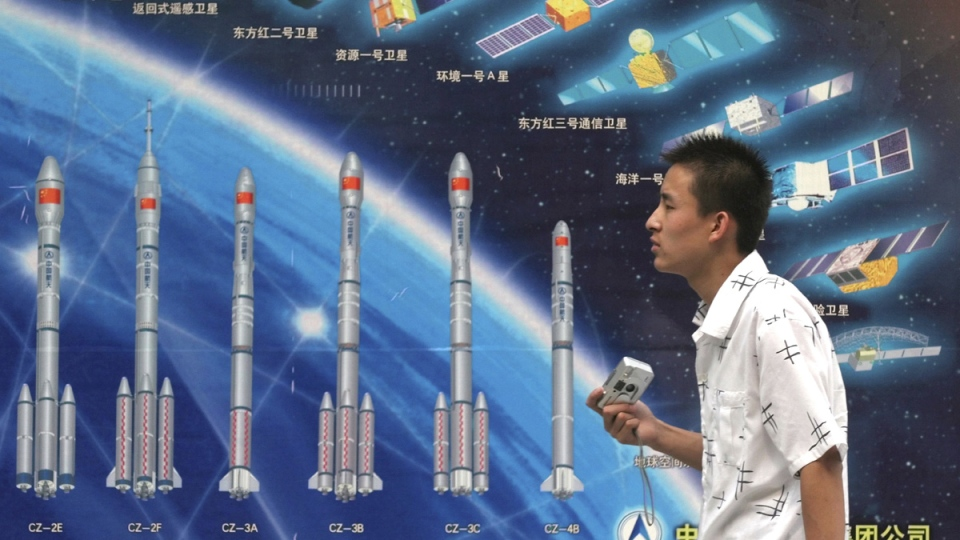 Walking past an illustration showing various Long March space rockets and satellites on exhibit at a local Beijing park in China, on Oct. 6, 2005. (AP)