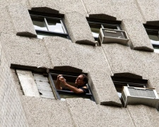 A firefighter surveys the scene where a slab of concrete fell from the 18th floor of a downtown hotel killing a woman and injuring her fiance in Montreal Thursday, July 16, 2009. (Ryan Remiorz / THE CANADIAN PRESS)