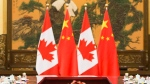 Canadian and Chinese flags are seen at the Great Hall of the People in Beijing, China on Monday, Dec. 4, 2017. (THE CANADIAN PRESS / Sean Kilpatrick)