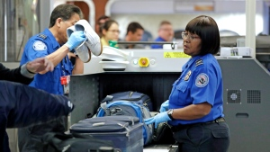 Transportation Security Administration (TSA) officers assist travelers with luggage through a security screening area during a partial federal government shutdown Monday, Dec. 31, 2018, in SeaTac, Wash. (File Photo/AP Photo/Elaine Thompson)
