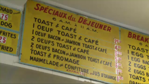 Handpainted menus still run along the top of the fryers at Decarie Hot Dog in St. Laurent, and a simple counter design allows the staff to build up a relationship with their customers. (CTV Montreal)