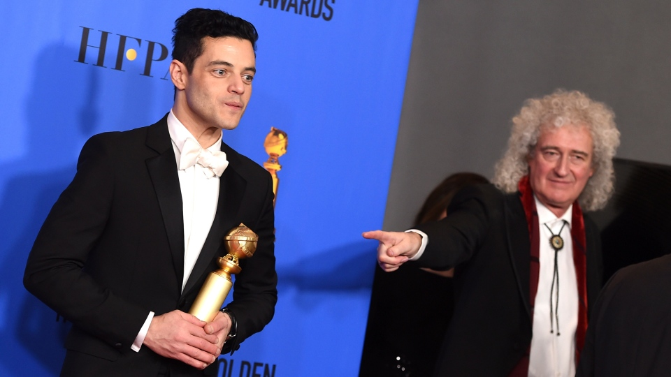 "Rami Malek poses in the press room with the award for best performance by an actor in a motion picture, drama for ""Bohemian Rhapsody"" at the 76th annual Golden Globe Awards at the Beverly Hilton Hotel on Sunday, Jan. 6, 2019, in Beverly Hills, Calif. Looking on at right is Brian May of Queen. (Photo by Jordan Strauss/Invision/AP)"