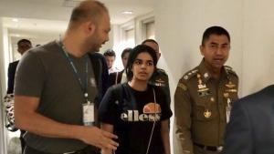 Chief of Immigration Police Maj. Gen. Surachate Hakparn, right, walks with Saudi woman Rahaf Mohammed Alqunun before leaving the Suvarnabhumi Airport in Bangkok on Jan. 7, 2019. (Immigration police via AP)