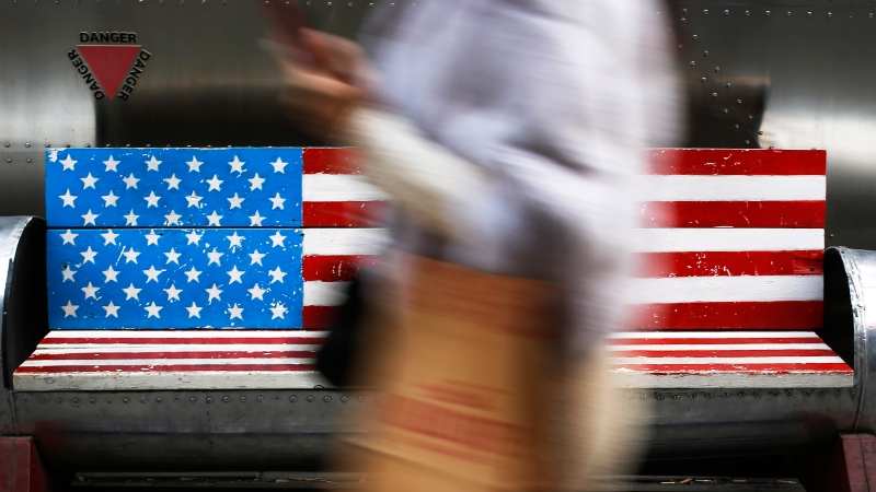 In this Sunday, Jan. 6, 2019, photo, a woman walks by a bench painted with the U.S. flag at the capital city's popular shopping mall in Beijing. (AP Photo/Andy Wong)