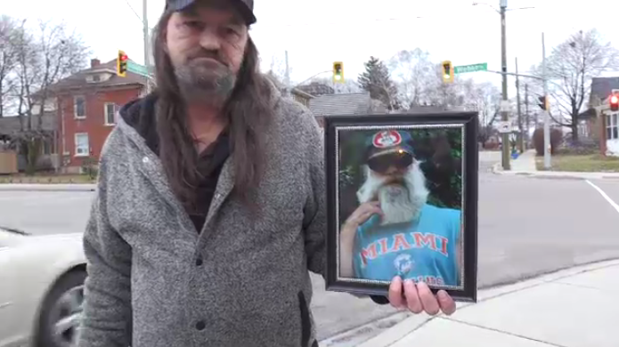 Rick Couckuit holds a photo of his deceased friend of almost a decade, Mark Billings.