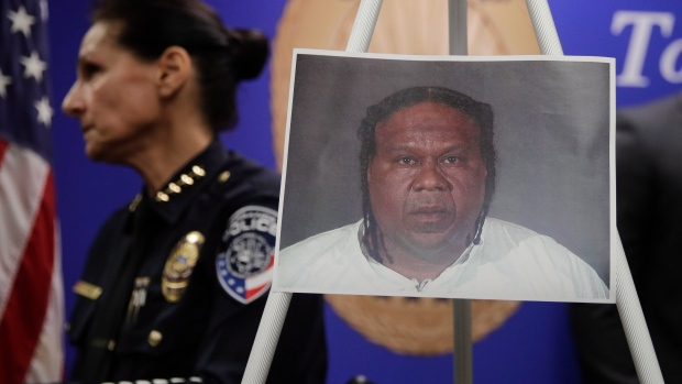 Torrance police Chief Eve Irvine walks past a photo of Reginald Wallace during a news conference Monday, Jan. 7, 2019, in Torrance, Calif. Wallace is arrested for a deadly shooting at a Southern California bowling alley. (AP Photo/Jae C. Hong)