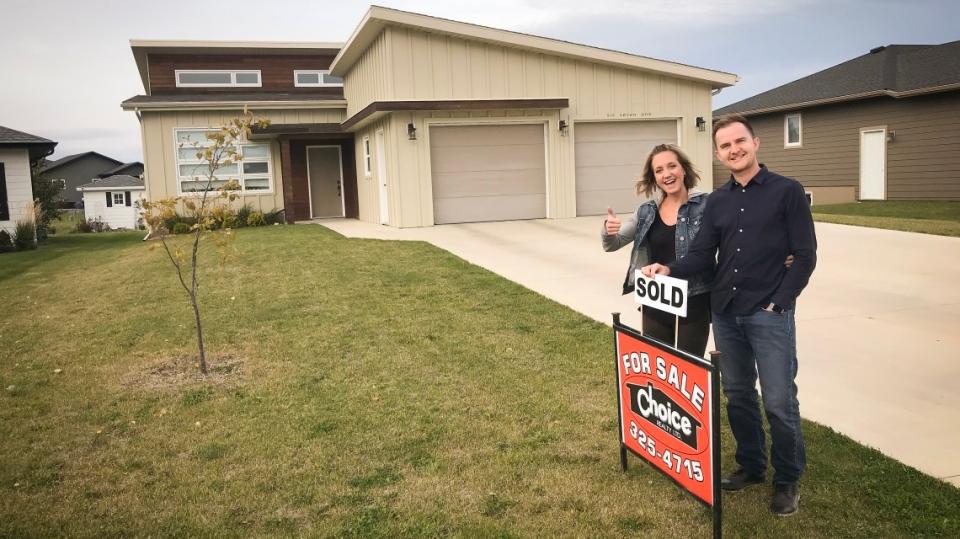 Alana and Rick Knelsen pose for a photograph after selling their home in  Winkler, Man. They and their two young children are leaving Canada behind  to become ...