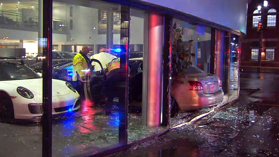 Emergency crews inspect a vehicle that crashed into a Porsche dealership in Toronto, Monday, Jan. 7, 2019.