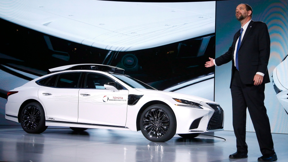 Gill Pratt, CEO of the Toyota Research Institute, unveils Toyota's latest autonomous-driving test vehicle for the Toyota Research Institute, called P4, based on the new-generation Lexus LS500h hybrid luxury sedan, with a roof-mounted assembly with cameras and sensors, and sensors added onto the front fenders, at the Toyota news conference at CES International Monday, Jan. 7, 2019, in Las Vegas. (AP Photo/Ross D. Franklin)