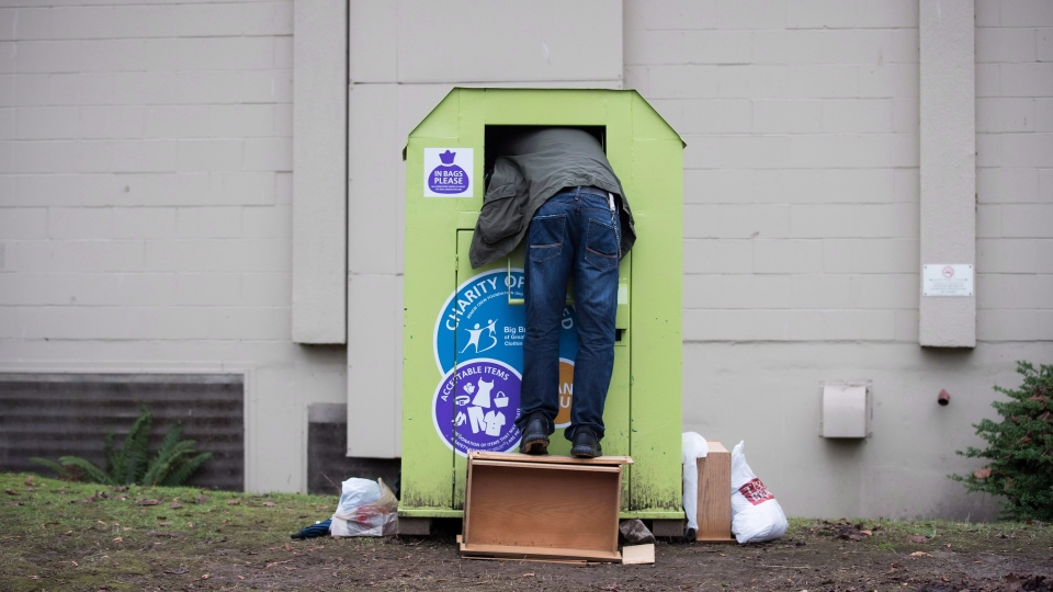 A man tries to retrieve items from a clothing donation bin in Vancouver, on Wednesday December 12, 2018. (THE CANADIAN PRESS/Darryl Dyck)