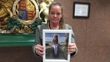 Jenny Devoe holding a photo of her daughter