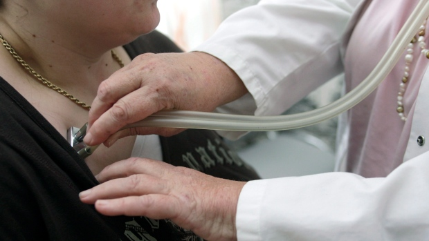 A doctor checks a patient with a stethoscope. THE CANADIAN PRESS/AP/Thomas Kienzle