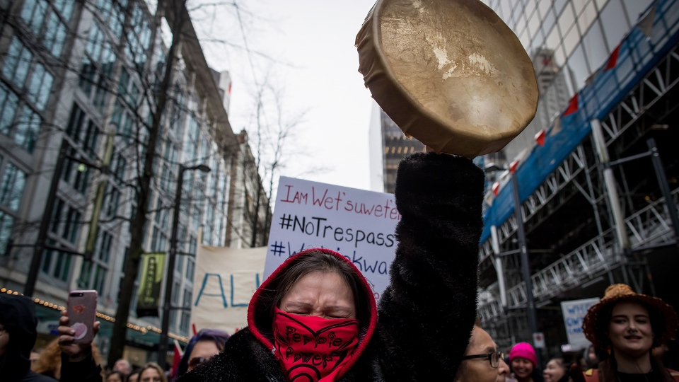 Tilly Innes, from the St'at'imc Nation, raises a drum in the air and cheers during a march in support of pipeline protesters in northwestern British Columbia, in Vancouver, on Tuesday, Jan. 8, 2019. THE CANADIAN PRESS/Darryl Dyck
