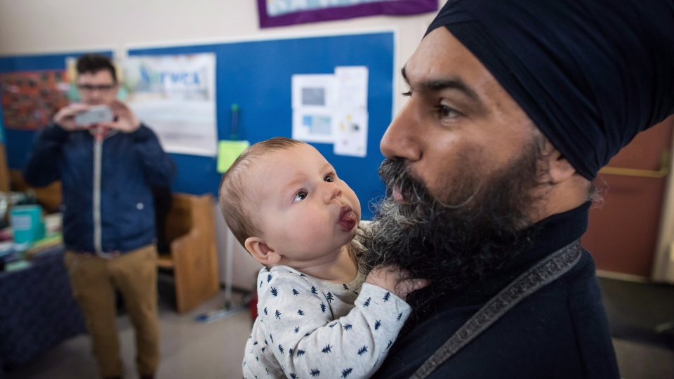 NDP Leader Jagmeet Singh holds Laurier LeSieur, 5 months, while speaking with his parents during a visit to the Rumble on Gray Street Fair, in Burnaby, B.C., on Saturday September 15, 2018. (THE CANADIAN PRESS/Darryl Dyck)