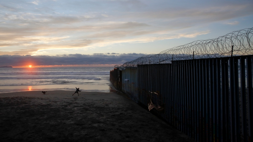 A man throws a ball for his dog Wednesday, Jan. 9, 2019, next to the border wall topped with razor wire in Tijuana, Mexico. (AP Photo/Gregory Bull)
