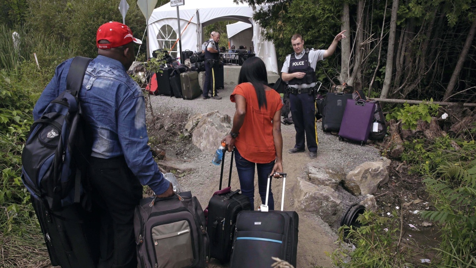 In this Aug. 7, 2017 file photo, an RCMP officer informs a migrant couple of the location of a legal border station, shortly before they illegally crossed from Champlain, N.Y., to Saint-Bernard-de-Lacolle, Quebec, using Roxham Road. THE CANADIAN PRESS/AP/Charles Krupa