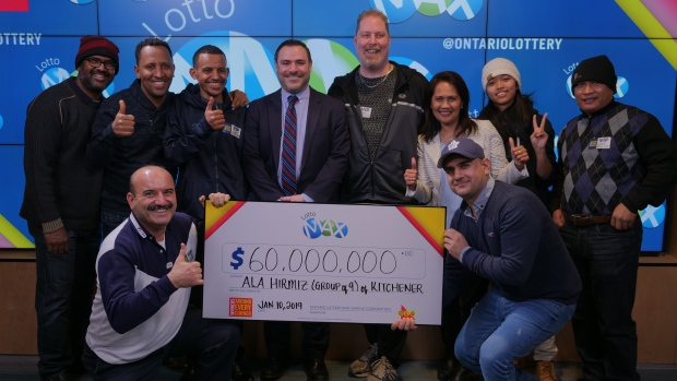 Nine co-workers posing with a $60 million cheque