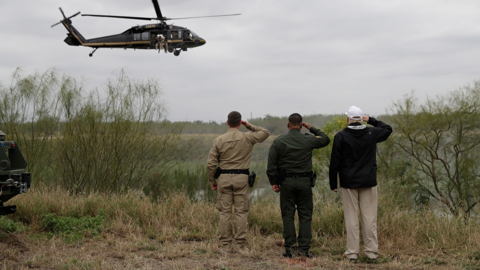 President Donald Trump salutes as a U.S. customs and Border Protection helicopter passes as he tours the U.S. border with Mexico at the Rio Grande on the southern border, Thursday, Jan. 10, 2019, in McAllen, Texas. (AP Photo/ Evan Vucci)