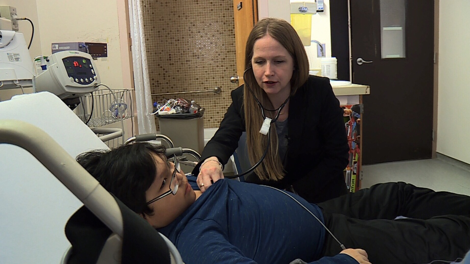 Dr. Tanya Holt, head of pediatric intensive care at the Royal University Hospital in Saskatoon, check on 12-year-old Quinton Kequahtooway as he recovers from a severe influenza virus infection. (CTV News)