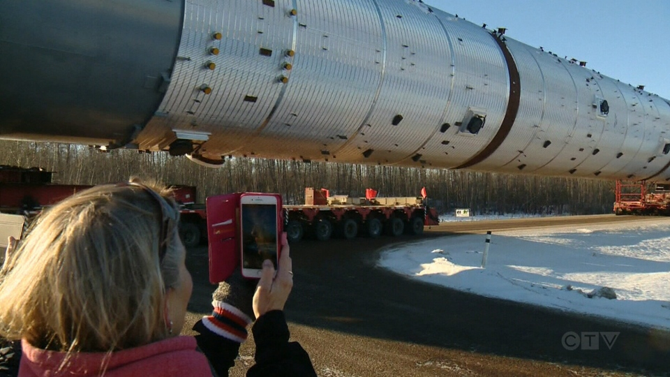 A woman takes a picture of the petrochemical splitter as it travels from an equipment manufacturer in Edmonton to a work site in Fort Saskatchewan, Alta.