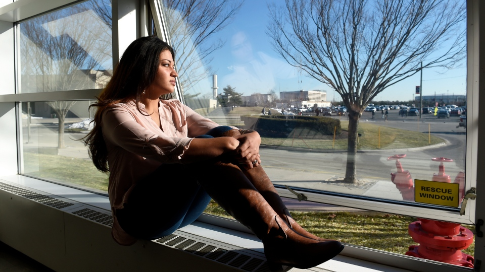 In this Feb. 2, 2016, file photo, Naila Amin, 26, looks out from a classroom window at Nassau Community College in Garden City, N.Y.(AP Photo/Kathy Kmonicek)