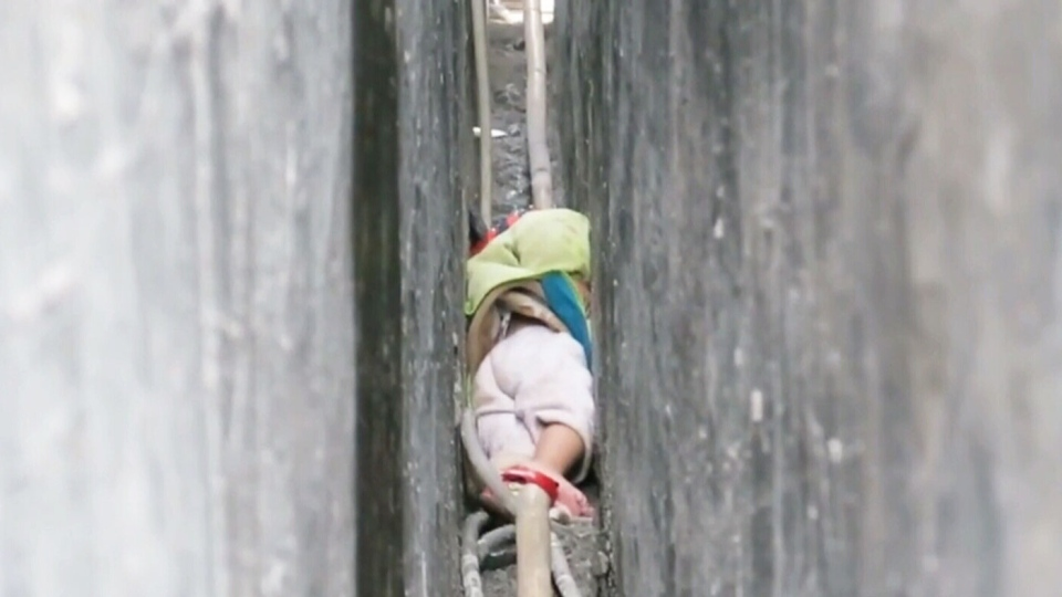 Firefighters freed a toddler trapped between a narrow gap between two buildings in southern China for nearly an hour, in a dramatic rescue that was captured on video. (Guigang Fire Department /Weibo)