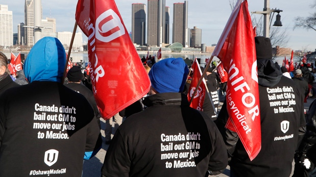Supporters for Unifor, the national union representing auto workers, attend a rally within view of General Motors headquarters, background, Friday, Jan. 11, 2019, in Windsor, Ont. Workers were protesting the closing of the Oshawa assembly plant, (AP Photo/Carlos Osorio)