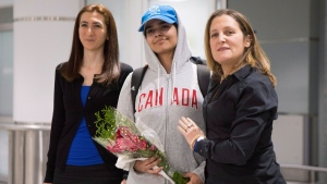 Saudi woman Rahaf Mohammed al-Qunun, centre, stands with Canadian Minister of Foreign Affairs Chrystia Freeland, right, as she arrives at Toronto Pearson International Airport, on Saturday, January 12, 2019.THE CANADIAN PRESS/Chris Young