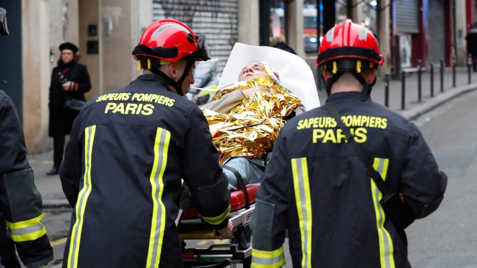 Firefighters evacuate a wounded man on a stretcher from the scene of a gas leak explosion in Paris, France, Saturday, Jan. 12, 2019. (AP Photo/Thibault Camus)