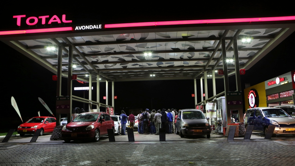 Motorists gather to express their anger after fuel ran out at a gas station in the capital Harare, Tuesday, Jan. 8, 2019. (AP Photo/Tsvangirayi Mukwazhi)