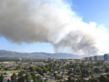 Smoke from a raging forest fire over Kelowna, B.C, which forced 3,000 residents from their homes on Saturday July 18, is shown. (Daniel Hayduk / THE CANADIAN PRESS)