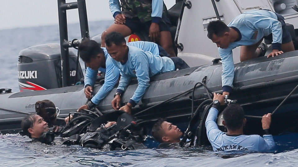 In this Oct. 30, 2018, file photo, Indonesian navy frogmen emerge from the water during a search operation for the victims of the crashed Lion Air plane in the waters of Tanjung Karawang, Indonesia. (AP Photo/Tatan Syuflana, File)