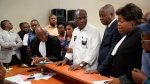 Accompanied by his wife and his lawyers, Congo opposition candidate Martin Fayulu, center, petitions the constitutional court following his loss in the presidential elections in Kinshasa, Congo, Saturday Jan. 12, 2019. The ruling coalition of Congo's outgoing President Joseph Kabila has won a large majority of national assembly seats, the electoral commission announced Saturday, while the presidential election runner-up was poised to file a court challenge alleging fraud. (AP Photo/Jerome Delay)