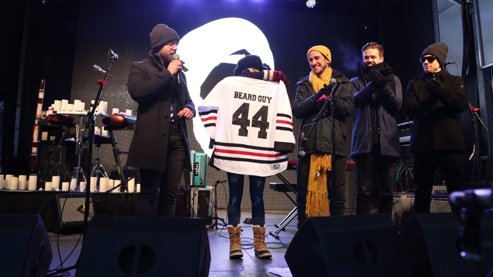 "Members of Walk Off the Earth hold a jersey donated by the Burlington Sound of Music Festival that is lettered for Mike ""Beard Guy"" Taylor Walk Off The Earth Memorial & Tribute Concert for Mike ""Beard Guy"" Taylor in Burlington, Ont., on Sunday, January 13th, 2019. Acoustic performances by members of Barenaked Ladies, Scott Helman, Monster Truck, USS and more were also scheduled for the event. THE CANADIAN PRESS/Peter Power"