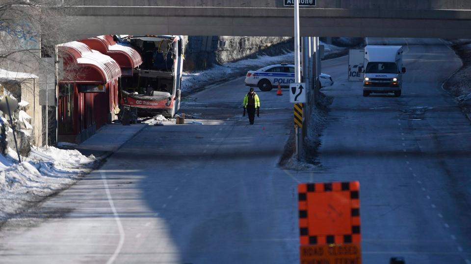 A police officer works at the scene where a double-decker city bus struck a transit shelter at the start of the afternoon rush hour on Friday, at Westboro Station in Ottawa, on Saturday, Jan. 12, 2019. (THE CANADIAN PRESS / Justin Tang)
