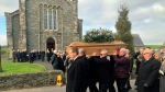 Mourners carry the coffin at the funeral of Ulster historian and politician Dr Ian Adamson at Conlig Presbyterian Church in County Down, Northern Ireland, Monday Jan. 14, 2019. (Michael McHugh/PA via AP)