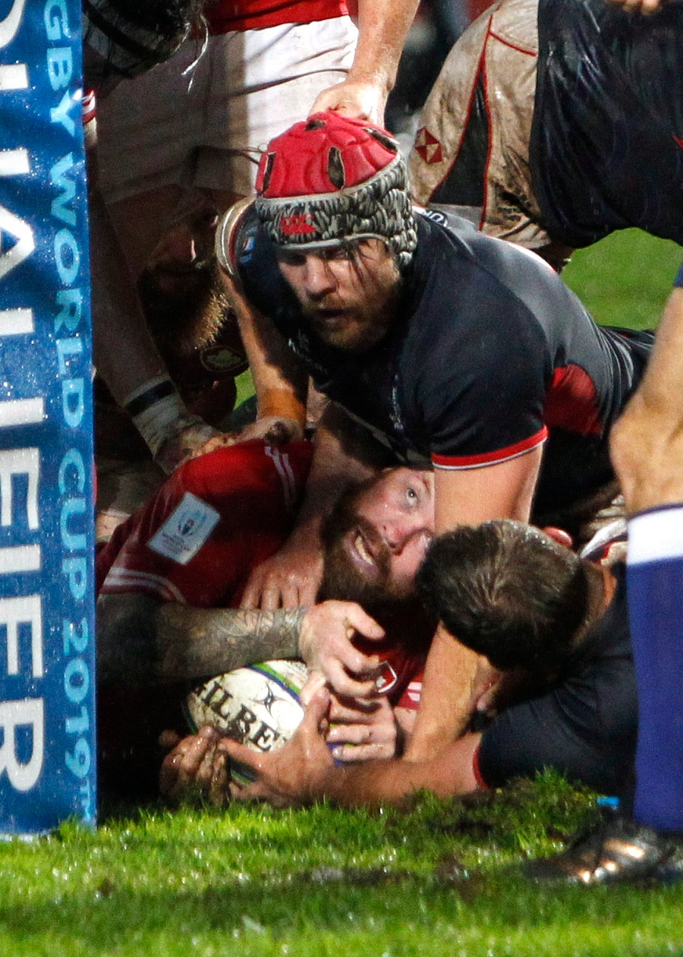 Canada's Ray Barkwill, bottom, scores a try despite Hong Kong's Fin Field during the 2019 Japan Rugby Union World Cup qualifying match between Canada and Hong Kong, in Marseille, southern France, Friday, Nov. 23, 2018. (AP Photo/Claude Paris)