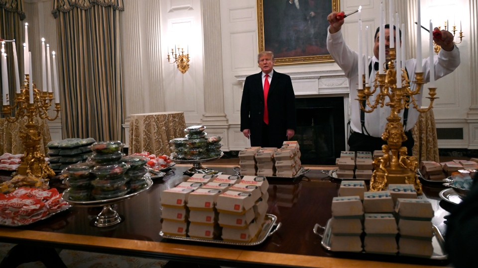 U.S. President Donald Trump talks to the press about the table full of fast food in the State Dining Room of the White House in Washington, Monday, Jan. 14, 2019, for the reception for the Clemson Tigers. (AP Photo/Susan Walsh)