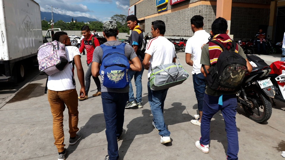 A group of young men arrive at a main bus station to join scores of other migrants forming a caravan to travel to the U.S. border, in San Pedro Sula, Honduras, Monday, Jan. 14, 2019. (AP Photo/Delmer Martinez)