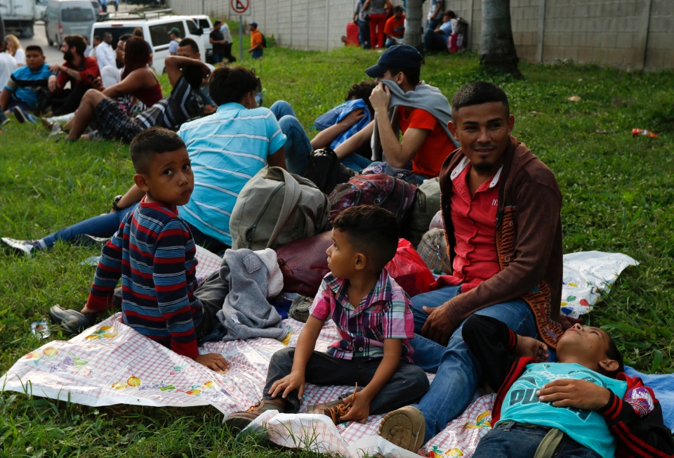 Freddy Rivas, second right, of Tocoa, Honduras, sits with his sons Josue, left, and Elkin, center, and his brother Mario, as they wait with scores of other migrants hoping to join a caravan to travel to the U.S. border, in San Pedro Sula, Honduras, Monday, Jan. 14, 2019. (AP Photo/Delmer Martinez)