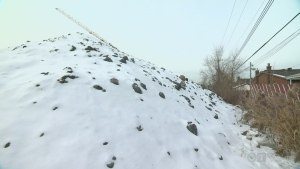 The snow-covered mountain of dirt and rocks is taller than adjacent homes on Cure de Rossi St. in Montreal's borough of LaSalle.