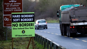 A poster against a hard border stands on the border between Northern Ireland and the Republic of Ireland near the town of Derrylin, Northern Ireland, Wednesday, Dec. 12, 2018. (AP Photo/Peter Morrison)