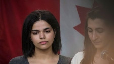 Saudi woman Rahaf Mohammed, left, stands next to her translator during a public statement at the COSTI Corvetti Education Centre in Toronto, Tuesday, January 15, 2019. THE CANADIAN PRESS/ Tijana Martin