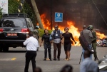 Security forces help civilians flee the scene as cars burn behind, at a hotel complex in Nairobi, Kenya Tuesday, Jan. 15, 2019. Extremists have launched an attack on a luxury hotel in Kenya's capital, sending people fleeing in panic as explosions and heavy gunfire reverberate through the neighborhood. (AP Photo/Ben Curtis)