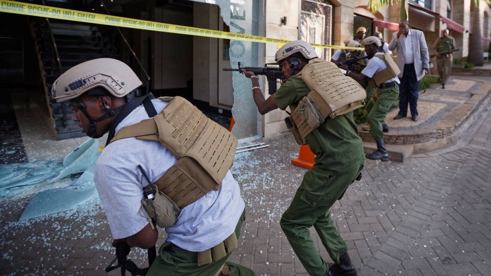 Security forces point their weapons through a shattered door behind which an unexploded grenade lies, at a hotel complex in Nairobi, Kenya, Tuesday, Jan. 15, 2019. (AP Photo/Ben Curtis)